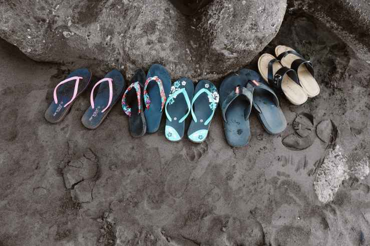 assorted flip flops on sand